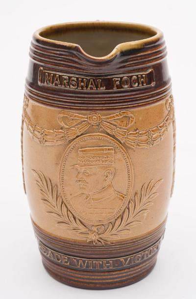 Of WWI interest a Royal Doulton stoneware jug of barrel shaped form with ribbed strap handle embossed with an oval portrait of Marshall Foch suspended from foliate swags and victors laurels and captioned with his name and 'Peace with Victory, circa 1919, 18.5cm high.