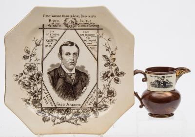 A Wallis & Gimson commemorative plate for Fred Archer of octagonal form and printed in black with a portrait of the jockey together with a list of the races won, 24cm wide, together with a pottery cream jug printed with a child on a dog and captioned 'The little Jockey'.