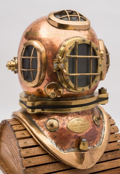 Sale SS2; Lot: 0051: A 2-bolt/3-bolt diving helmet by Siebe Gorman & Co, London, matching numbers '202' and '3090', oval top and side windows with guards, hinged oval faceplate with guard, wing nut spitcock, fitted double purge valves, one to either side, rear air intake and internal ducts, weight hangers and manufacturer's plaque to corselet with one piece two bolt brail, 52cm high.