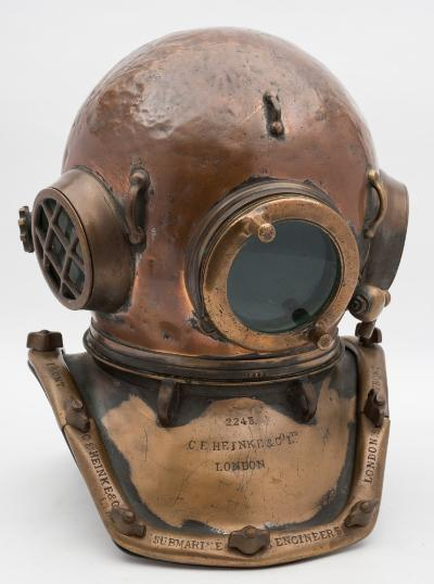 Sale SS2; Lot: 0062: A 12-bolt square corselet 'Pearler' diving helmet by CE Heinke & Co Ltd, London, number '2243' (matching), triple circular windows with screw in guards to side windows, three tie offs, spitcock, rear air inlet and wheel adjust outlet with head button, re-positioned telephone 'banjo' retaining nut, the counter struck corselet with hoop hangers and stamped as per title, 46cm high.