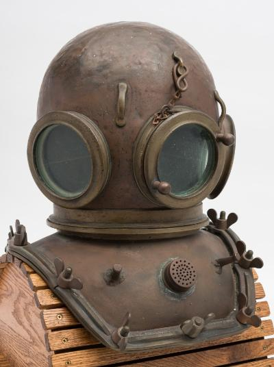Sale SS2; Lot: 0064: An early 12-bolt square corselet diving helmet by CE Heinke Sub Marine Engineer, Gt. Portland Street, London, stamped number '2', three circular observation windows, the front window with safety chain, lashing eyes above, rear air inlet, outlet valve to the rear of the left side window, thumb screw lock to the rim, the corselet with centre mounted outlet valve, flanked by copper bar weight hangers, the brails with reinforcing ridges and wing nuts stamped as per title, 47cm high. *Note - CE Heinke were at this address from 1860 until 1904.