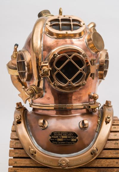 Sale SS2; Lot: 0087: A US Navy MK V Helium MOD-1 diving helmet by Morse Diving Equipment Co, Boston, number '358' (matching) the four observation windows with guards, the front window hinged to one side, outlet control to lower left with banana valve to crown and outlet exhaust, the safety catch moved to the front of the helmet to accommodate the large scrubbing chamber with Oxy/Helium inlet, the crown with central lifting eye surrounded by standard air inlet, capped comms and electrical connection for heated underwear, the corselet with maker's plate as per title dated '12.01.05', breastplate eyes and brass brails, 56cm high.