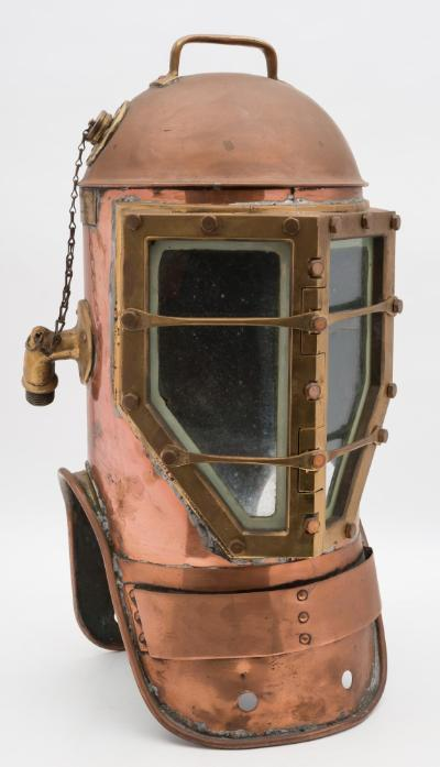 A Miller Dunn 'Divinhood' Navy Standard (style two) shallow water diving helmet by Miller Dunn, Miami, brass handle to top, with circular comms connection cap and safety chain, side air intake, squared and angled front windows with double bar guards, stamped 'B12' to the window surround, copper weight mounts to front and back, 61cm high. See page 3, vol 1, 'Diving Helmets and Equipment Through the Ages'.