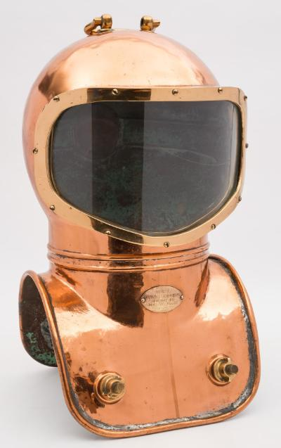 A shallow water diving helmet by Morse Diving Equipment Company Inc, Boston, USA, number '6308', folding brass handle to top over a single pentagonal panoramic window, rear air inlet and side tie off, maker's plate to breastplate as per title, the front and rear weight posts threaded and secured with corselet nuts, 59cm high handle raised.