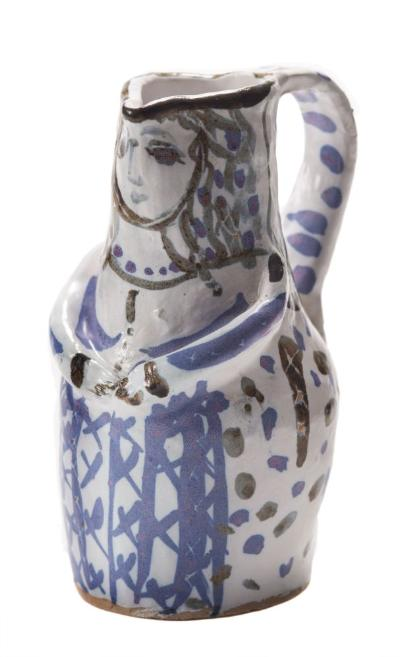 Lydia Corbett [b 1934] - a stoneware jug in the form of a female figure, decorated in black and pale lilac tones on an ivory ground, impressed personal seal at base of handle, 21cm high.